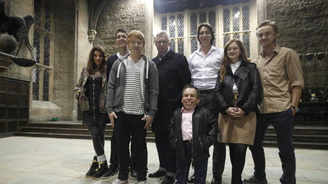 "Actors from the Harry Potter movie series, from left Natalia Tena, Oliver Phelps, Rupert Grint, Mark Williams, Warwick Davis, James Phelps, Bonnie Wright, and Tom Felton, poses for photographs at the 'Great Hall' one of the sets of the movies during a tour in Watford, north of London, Wednesday Oct. 12, 2011. This collection of sheds and sound stages, a former aerodrome near London is where the eight films were shot over almost a decade, and soon they will be home to the official ""Making of Harry Potter"" studio tour. With more than five months to go until the site's March 31, 2012 opening, tickets go on sale Thursday Oct. 13, 2011. The eight Potter films made here between 2001 and 2010 were a mini-industry, employing both the cream of Britain's acting talent and hundreds of craftspeople and technicians. The tour will show off the skill and craftsmanship that went into the spectacle. (AP Photo/Lefteris Pitarakis)"