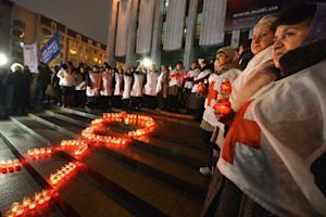 Activist and HIV infected people holds candles as they …