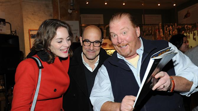 Mario Batali, right, shows off his guest-edited April issue of FOOD & WINE to actor Stanley Tucci, center, and wife Felicity Blunt during a party at Eataly in New York, Wednesday, March 6, 2013.  (Photo by Diane Bondareff/Invision for FOOD & WINE/AP Images)