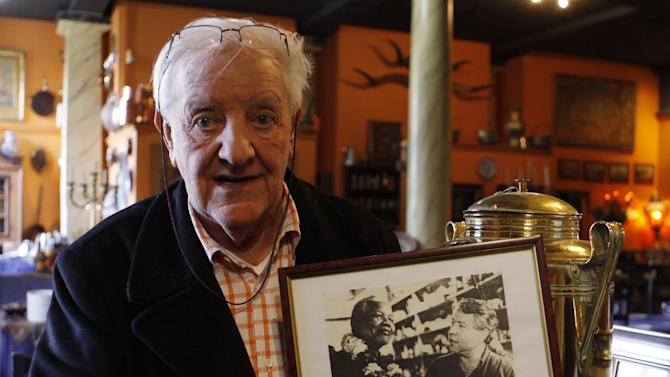 In this photo taken Tuesday, July 16 2013, Eduan Naude, poses with photos of celebrities, including former president Nelson Mandela, front left, with co-owner and partner, Brian Shalkoff, in the Gramadoelas restaurant. The restaurant, which drew global figures as clients, is closing at the end of the month after the murder of Shalkoff. (AP Photo/Denis Farrell)