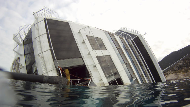 View of the bow of the grounded cruise ship Costa Concordia off the Tuscan island of Giglio, Italy, Friday, Jan. 27, 2012. Costa Crociere SpA offered uninjured passengers €11,000 ($14,460) apiece to compensate them for lost baggage and the psychological trauma they suffered after their cruise ship ran aground and capsized off Tuscany. But some passengers are already refusing to accept the deal, saying they can't yet put a figure on the costs of the trauma they endured. Costa announced the offer after negotiations with consumer groups who say they are representing 3,206 passengers from 61 countries who suffered no physical harm when the massive Costa Concordia cruise ship hit a reef on Jan. 13. In addition to the lump-sum indemnity, Costa, a unit of the world's biggest cruise operator, the Miami-based Carnival Corp., also said it would reimburse uninjured passengers the full costs of their cruise, their return travel expenses and any medical expenses they sustained after the grounding. (AP Photo/Pier Paolo Cito)