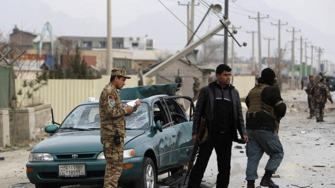 Afghan security personnel inspect a civilian's car at the site of a bomb attack in Kabul