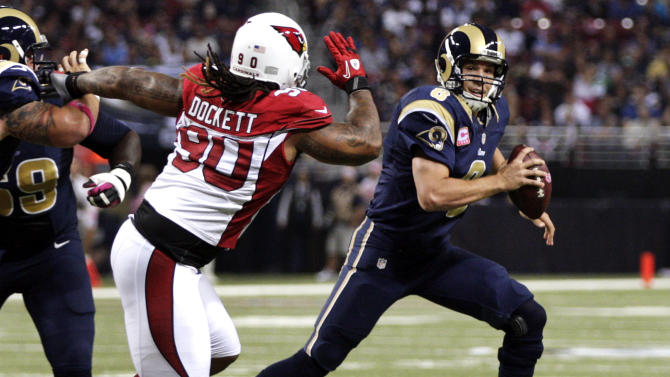 St. Louis Rams quarterback Sam Bradford, right, scrambles as Arizona Cardinals defensive end Darnell Dockett gives chase during the first quarter of an NFL football game, Thursday, Oct. 4, 2012, in St. Louis. (AP Photo/Tom Gannam)
