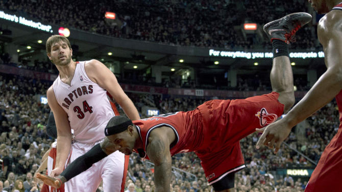 Miami Heat forward LeBron James, right, falls to the floor after trying to dunk over Toronto Raptors center Aaron Gray, left, during first half NBA basketball action in Toronto on Sunday Feb. 3, 2013. (AP Photo/THE CANADIAN PRESS,Frank Gunn)