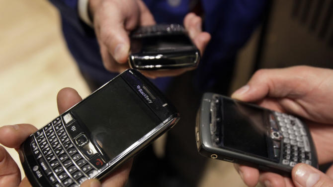 FILE- In this Wednesday, May 30, 2012, file photo, three people on the floor of the New York Stock Exchange display their Blackberry smartphones. Struggling BlackBerry maker Research In Motion says Wednesday, June 20, 2012, it has started laying off employees as part of a restructuring plan aimed at saving about $1 billion this year. (AP Photo/Richard Drew)