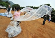 This file photo shows former North Korean defectors living in South Korea preparing to launch balloons carrying anti-Pyongyang leaflets across the border in Gimpo, northwest of Seoul, in June. S.Korean troops and riot police on Monday prevented activists from launching more leaflets, after North Korea threatened a 'merciless' military response