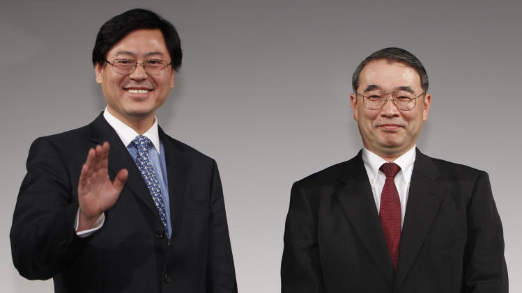 Lenovo Group Chief Executive Officer Yang Yuanqing, left, waves at photographers after shaking hands with NEC President Nobuhiro Endo during a joint press conference in Tokyo Thursday, Jan. 27, 2011. NEC and China's Lenovo said Thursday they will join forces to create the largest personal computer business in Japan. (AP Photo/Shizuo Kambayashi)