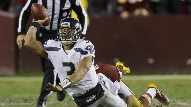 Seattle Seahawks quarterback Russell Wilson passes the ball as he's dragged down by Washington Redskins strong safety Reed Doughty during the second half of an NFL wild card playoff football game in Landover, Md., Sunday, Jan. 6, 2013. (AP Photo/Matt Slocum)