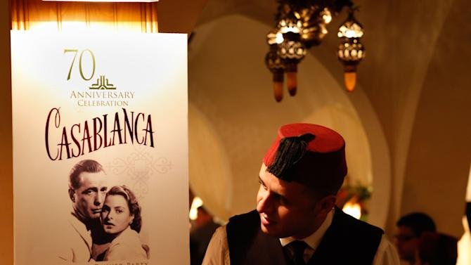 """A Rick's Cafe's server looks at the poster announcing the 70th anniversary tribute to the 1942 movie """"Casablanca"""" , in Casablanca, Morocco, Saturday, Nov. 24, 2012.  A former U.S. diplomat spent two years of work and a million dollars in investments to bring Rick's Cafe to Morocco's largest city. The elegant nightclub where Humphrey Bogart pined for Ingrid Bergman was just a set on a Warner Bros. sound stage in California, the film crew never got anywhere near North Africa. (AP Photo/Abdejalil Bounhar)"""