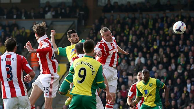 Norwich City's Bradley Johnson, center, scores his team's opening goal during their English Premier League soccer match against Stoke City at Carrow Road, Norwich, England, Saturday, March 8, 2014