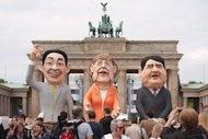 "<p>Effigies of (from left) German Economy Minister Philipp Roesler, German Chancellor Angela Merkel and German Social Democrats (SPD) chairman Sigmar Gabriel in front of the Brandenberg Gate in Berlin on Wednesday. Merkel is opposed for calls to allow the issuance of eurobonds, seeing them as ""wrong and counterproductive.""</p>"