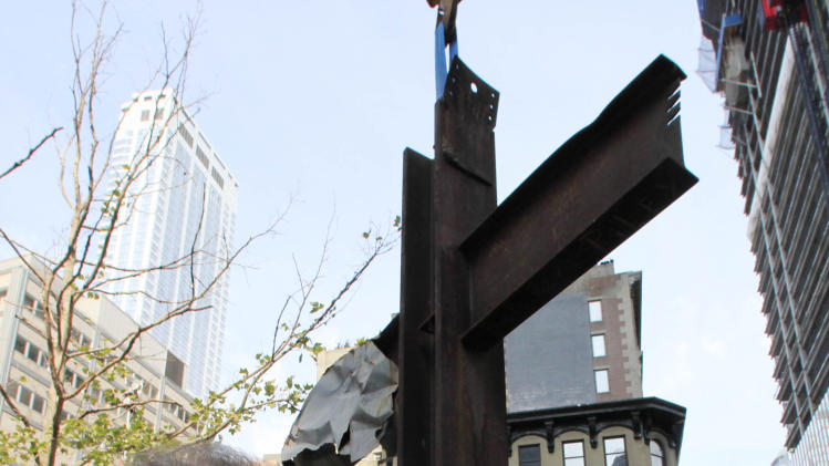 Frank Silecchia, left, and former New York Mayor Rudolph Giuliani embrace following a ceremony for the September 11 cross, Saturday, July 23, 2011, in New York.  After the ceremony, the cross was installed at the National September 11 Memorial and Museum. Silecchia discovered the cross upright in the ruins of ground zero following the attacks of Sept. 11, 2001. (AP Photo/Mark Lennihan)