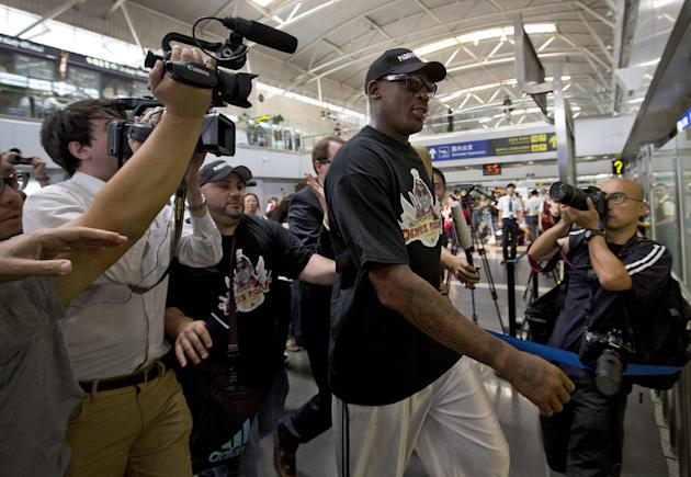 Former NBA star Dennis Rodman, center, is surrounded by media as he arrives at the departure hall of Beijing International Capital Airport in Beijing Tuesday, Sept. 3, 2013. Rodman is heading to North