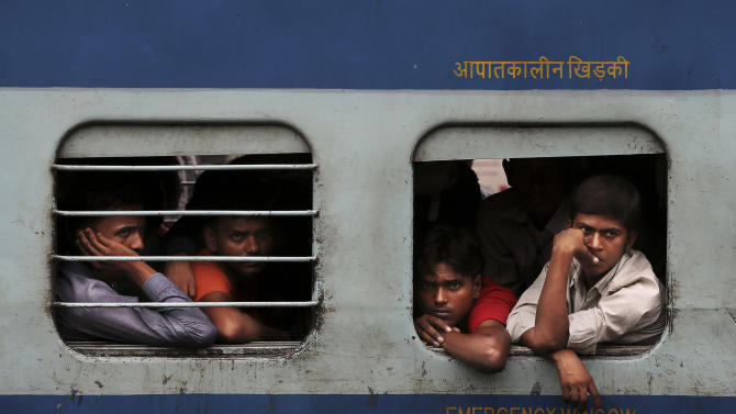 Indian stranded passengers wait inside a stalled train as they wait for the services to resume after a power outage in New Delhi, India, Tuesday, July 31, 2012. India's energy crisis cascaded over half the country Tuesday when three of its regional grids collapsed, leaving 620 million people without government-supplied electricity for several hours in, by far, the world's biggest blackout. Hundreds of trains stalled across the country and traffic lights went out, causing widespread traffic jams in New Delhi. (AP Photo/Kevin Frayer)