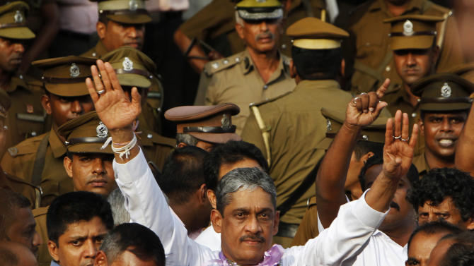 Sri Lanka's former army chief Sarath Fonseka waves to his supporters as he walks out of a jail in Colombo, Sri Lanka, Monday, May 21, 2012. Fonseka's release came after Foreign Minister G.L. Peiris met with U.S. Secretary of State Hillary Rodham Clinton on Friday in Washington, with the protection of human rights highlighted in their meeting. The U.S. has called Fonseka a political prisoner. Fonseka had been credited with leading Sri Lanka's army to victory in the country's long and bloody civil war against ethnic Tamil rebels, but he was jailed after challenging President Mahinda Rajapaksa in 2010 elections. (AP Photo/Gemunu Amarasinghe)