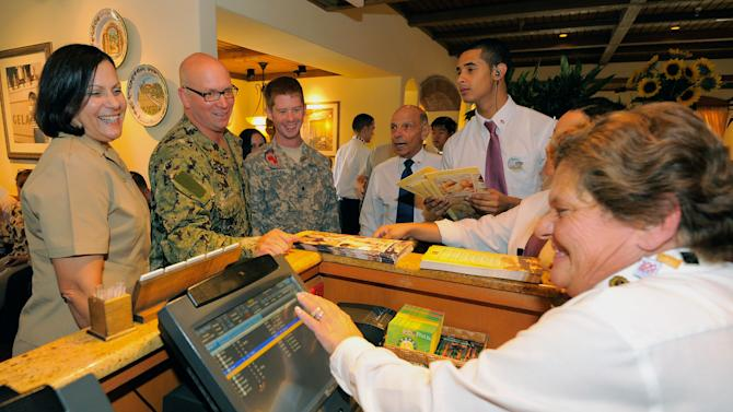 IMAGE DISTRIBUTED FOR DARDEN - Members of the Olive Garden staff in Kissimmee, Fla., welcome veterans and active-duty members of the military into the restaurant on Veterans Day. Olive Garden, Red Lobster and LongHorn Steakhouse are saluting those who serve our country by providing a variety of free menu items to veterans and active-duty military on Sunday, Nov. 11. 2012. (Scott A. Miller/AP Images for Darden)