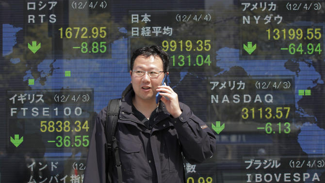 A man talks on a mobile phone in front of the electronic stock board of a securities firm in Tokyo Wednesday, April 4, 2012. Asian stock markets on Wednesday followed Wall Street into negative territory after the Federal Reserve voiced concern about U.S. job growth but appeared to refrain from taking steps to prop up the economy. The Nikkei index briefly slipped to 9,886.34, its lowest level in a month. Markets in mainland China, Hong Kong and Taiwan were closed for public holidays. (AP Photo/Itsuo Inouye)