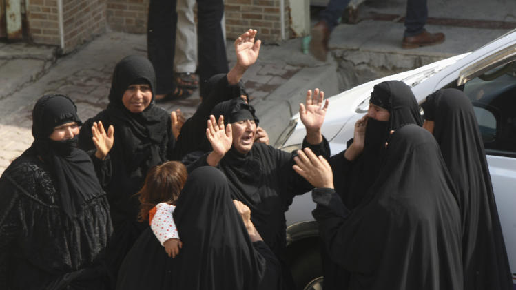 Mourners grieve for their relatives, who were victims killed in a bomb attack in Baghdad, during a funeral in Najaf