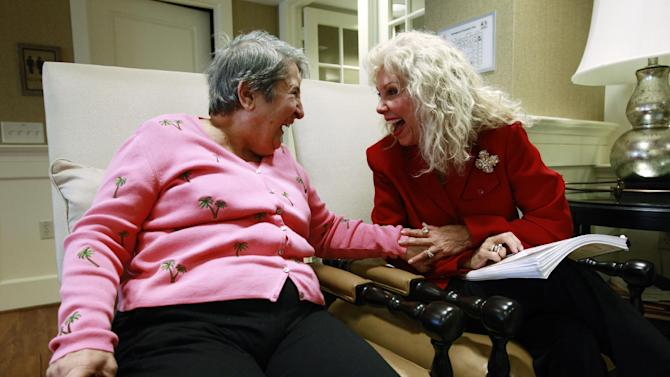 FILE-In this Monday, Feb. 6, 2012, file photo, Alexis McKenzie, right, executive director of The Methodist Home of the District of Columbia Forest Side, an Alzheimer's assisted-living facility, laughs with resident Catherine Peake, in Washington. Combined results released, Monday, Oct. 8, 2012, from two studies of an experimental Alzheimer's drug under development by Eli Lilly & Co. called solanezumab, suggest that it might modestly slow mental decline, especially in patients with mild disease. Taken separately, the studies missed their main goals to significantly slow the mind-robbing disease. But pooled results found 34 percent less decline in mild Alzheimer's patients compared to those on a dummy treatment for 18 months. (AP Photo/Charles Dharapak)