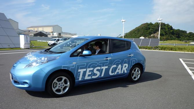 In this Friday, Oct. 12, 2012 photo, a Nissan staff driver, partially seen at left, of a Leaf electric vehicle, releases his hands from the steering wheel as he shows automated steering parking technology at the Japanese automaker's test ground in Yokohama, south of Tokyo. In the demonstration the vehicle turned on its own and backed into a charging station. The car is potentially capable of parking itself, even without a driver, according to Nissan. (AP Photo/Yuri Kageyama)