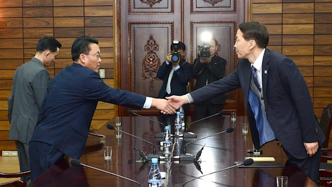 South Korean chief delegate Kim Ki-Woong (right) shakes hands with his North Korean counterpart Hwang Chol during their meeting at the truce village of Panmunjom, on November 26, 2015