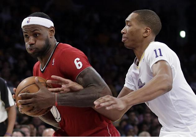 Miami Heat forward LeBron James, left, is fouled by Los Angeles Lakers guard Wesley Johnson during the second half of an NBA basketball game in Los Angeles, Wednesday, Dec. 25, 2013