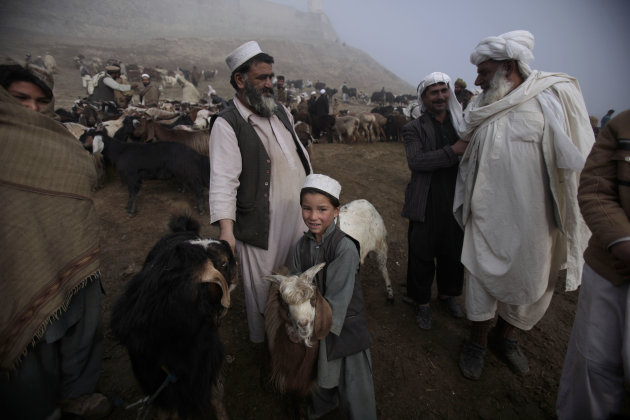 An Afghan boy holds his goat while his father, center, talks with a customer, right, at an open livestock market for the upcoming Eid-al-Adha festival, in Kabul, Afghanistan, Friday, Nov. 4, 2011. (AP Photo/Muhammed Muheisen)