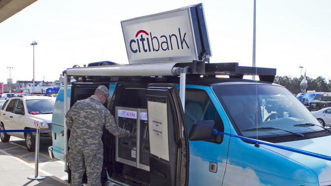 A customer is seen using the Citibank Mobile ATM Van, on Tuesday, Nov. 6, 2012 in Rockaway Park in the Borough of Queens, NY. (Photo by Mark Von Holden/Invision for Citibank/AP Images)
