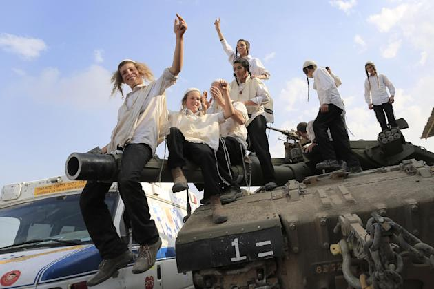 Ultra-Orthodox Jews of the Bratslav Hasidic sect, that gathered to show support for the forces, dance as they celebrate atop of a tank in southern Israel, close to the Israel Gaza Strip Border, Thursd