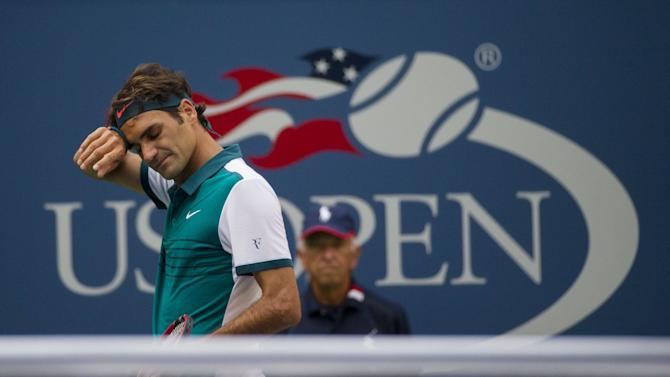 Federer of Switzerland wipes his brow during his match with Mayer of Argentina in their first round match at the U.S. Open Championships tennis tournament in New York