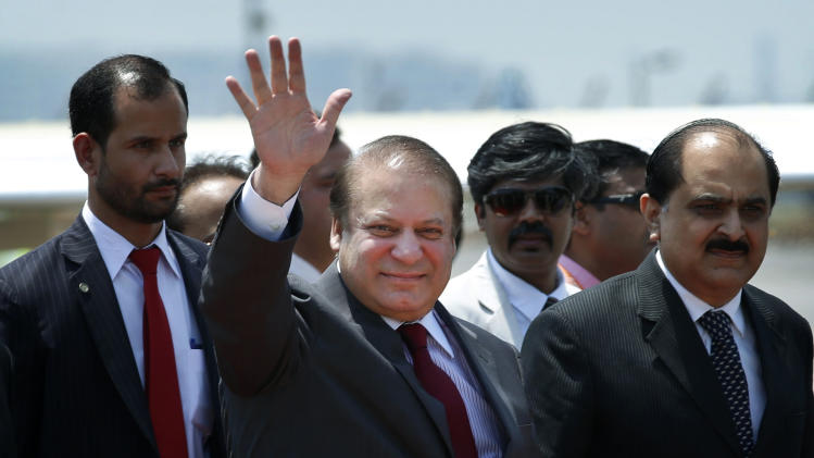 Pakistani Prime Minister Nawaz Sharif waves as he arrives to attend the swearing in ceremony of India's prime minister elect Narendra Modi in New Delhi, India, Monday, May 26, 2014. Sharif arrived in the capital of his country's archrival Monday to attend the inauguration of his Indian counterpart, a historic moment that could signal a thaw in relations between the often hostile neighbors. (AP Photo/Saurabh Das)