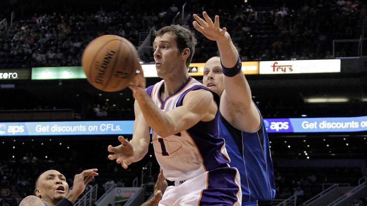 Phoenix Suns' Goran Dragic (1), of Slovenia, passes around the reach of Dallas Mavericks' Chris Kaman during the second half of an NBA basketball game, Thursday, Dec. 6, 2012, in Phoenix. (AP Photo/Matt York)