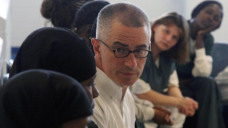 FILE - In this Tuesday, Aug. 2, 2011 file photo, former New Jersey Gov. James McGreevey, center, listens as an inmate speaks to a gathering of women inmates at Integrity House, a transitional housing and residential treatment area for women incarcerated at the Hudson County Correctional Center, in Kearney, N.J. The jailhouse treatment program where McGreevey works has earned a spot at the Sundance Film Festival and accolades from the U.S. Justice Department. McGreevey is spiritual counselor to 40 women in a pilot program to keep them from returning to jail. The Justice Department cites the program as one of two top re-entry efforts nationwide. The struggles of the women as well as McGreevey's own admission that he is gay and resignation as governor are the subject of a documentary showing at the Sundance Film Festival in January.  (AP Photo/Mel Evans, File)