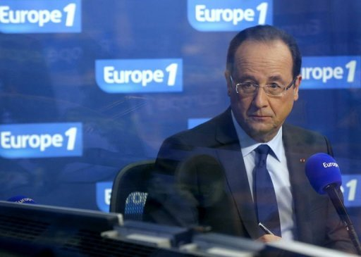 French president Francois Hollande is seen through the glass of an Europe 1 radio station studio on December 21, 2012 in Paris. Hollande Wednesday ordered tightened security for French nationals in the Central African Republic after violent protests denouncing the former colonial ruler for failing to help stem a rebel offensive.