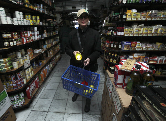 A woman shops for groceries by flashlight in the Tribeca neighborhood of New York, Tuesday, Oct. 30, 2012. ConEd cut power to some neighborhoods served by underground lines as the advancing storm surg