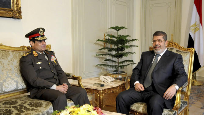 FILE - In this Thursday Feb, 21, 2013 file photo, released by the Egyptian Presidency, Egyptian Minister of Defense, Lt. Gen. Abdel-Fattah el-Sissi, left, meets with Egyptian President Mohammed Morsi at the presidential headquarters in Cairo, Egypt. With the Islamist President by his side, Egypt's army chief warned against slandering the military, denying in remarks broadcast Friday, April 12, 2013 that the military committed any abuses against protesters during the turbulent transition of the past two years. El-Sissi spoke following a late night meeting Thursday between the country's top brass and Islamist President Mohammed Morsi.(AP Photo/Mohammed Abd El Moaty, Egyptian Presidency, File )