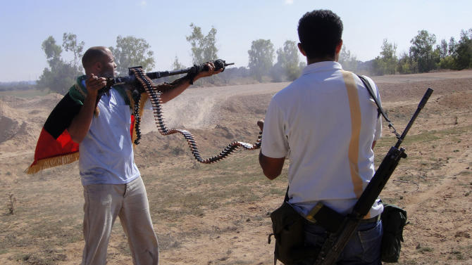 CORRECTS PHOTOGRAPHER TO STRINGER - Rebel fighters fire their machine guns towards pro-Moammar Gadhafi forces at the front line of Dafniya about 25 miles (40 kilometers) west of Misrata, Libya, Wednesday , June 15, 2011. (AP Photo)