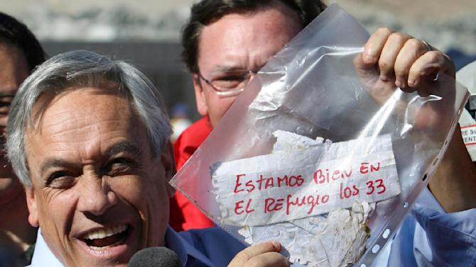 "FILE - In this Aug. 22, 2010 file photo, Chile's President Sebastian Pinera holds up a plastic bag containing a message, from miners trapped in a collapsed mine, that reads in Spanish ""We are ok in the refuge, the 33 miners"" in Copiapo, Chile. Chile marks on Sunday, Aug. 5, 2012 the two year anniversary since 33 miners were trapped in the mine that collapsed and trapped them for 69 days before their rescue. (AP Photo/Hector Retamal, File)"