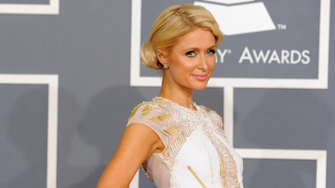 FILE - In a Feb. 12, 2012 file photo, Paris Hilton arrives at the 54th annual Grammy Awards in Los Angeles. An attorney for Roy Lopez Jr., charged with burglarizing Hilton's home, is seeking the case's dismissal on Friday, July 20, 2012, arguing that the lead officer's paid involvement in a Sofia Coppola movie about the break-ins has compromised the case. (AP Photo/Chris Pizzello, File)