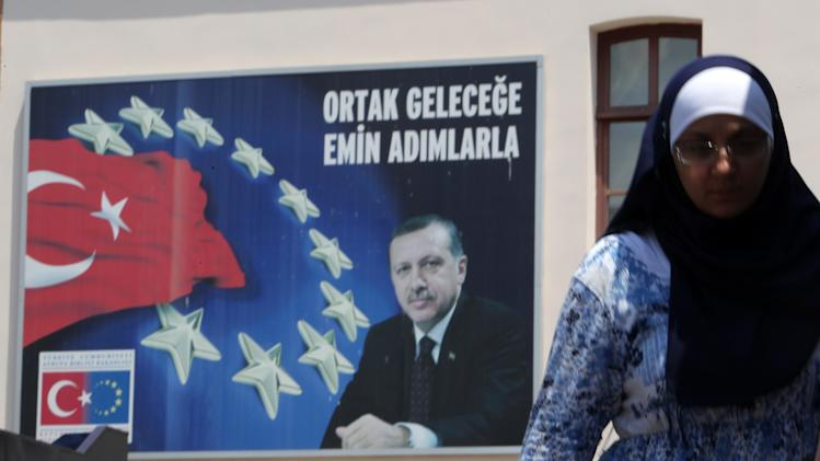 A woman walks next to a poster with a photo of Turkish Prime Minister, Recep Tayyip Erdogan, and the Turkish and European Union flags with the slogan ''Walking steadily to a joint future'' in Istanbul, Tuesday, June 4, 2013. Thousands have joined anti-government rallies across Turkey since Friday, when police launched a pre-dawn raid against a peaceful sit-in protesting plans to uproot trees in Istanbul's main Taksim Square. Since then, the demonstrations by mostly secular-minded Turks have spiraled into Turkey's biggest anti-government disturbances in years, and have spread to many of the biggest cities. (AP Photo/Thanassis Stavrakis)