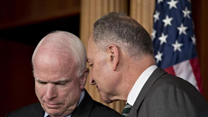 Sen. John McCain, R-Ariz., left, and Sen. Charles Schumer, D-N.Y., right, confer as they and other leading senators announce that they have reached agreement on the principles of sweeping legislation to rewrite the nation's immigration laws, during a news conference at the Capitol in Washington, Monday, Jan. 28, 2013. The deal covers border security, guest workers and employer verification, as well as a path to citizenship for the 11 million illegal immigrants already in this country.  (AP Photo/J. Scott Applewhite)