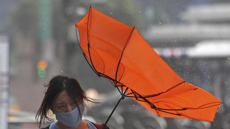 A woman holds her umbrella while walking against strong winds as Typhoon Matmo hits Taiwan, in Taipei
