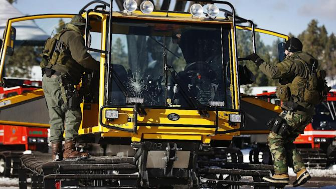 San Bernardino County Sheriff's deputies board a snow cat at the command post in Big Bear Lake, Calif., Saturday, Feb. 9, 2013. Clear skies allowed aircraft with heat-sensing technology to aid scores of officers searching in the snow-covered San Bernardino Mountains for Christopher Dorner, the former Los Angeles police officer suspected of killing three people in a vengeance-fueled rampage aimed at those he blames for ending his career. (AP Photo/Jae C. Hong)
