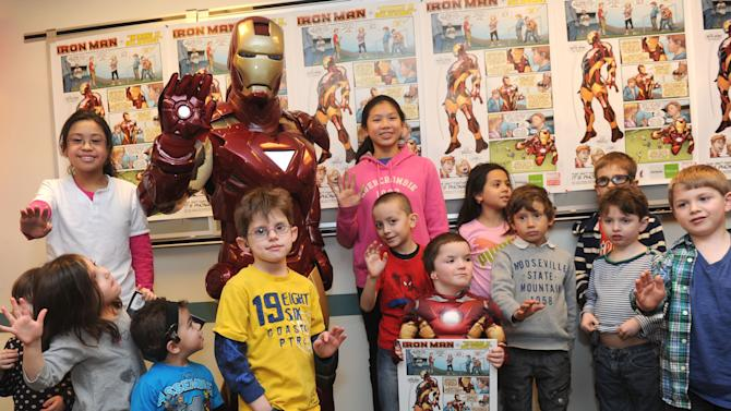 IMAGE DISTRIBUTED FOR PHONAK - Phonak hearing aid wearer Anthony Smith, 5, with poster, of Salem, NH, and kids from the Center for Hearing and Communication in New York City join Marvel's Iron Man, Tuesday, Feb. 26, 2013, to unveil a poster developed in partnership between Phonak and Marvel Custom Solutions that will be helpful in removing the stigma associated with children wearing hearing aids. (Photo by Diane Bondareff/Invision for Phonak)