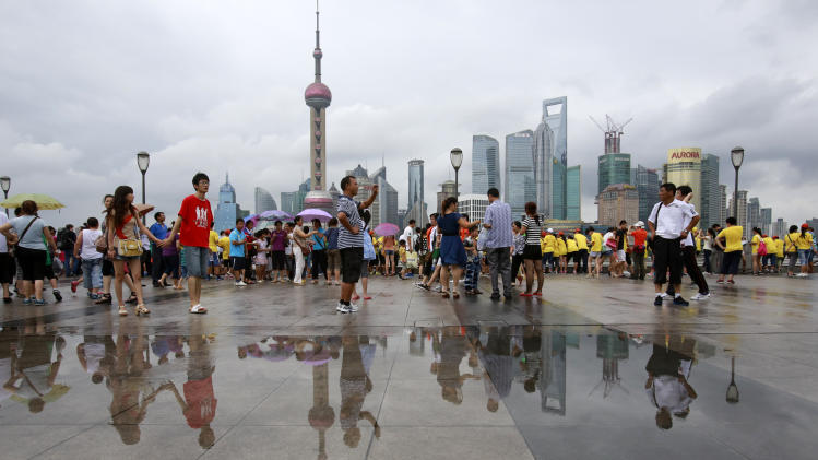 Visitors watch the scenery from the Bund, one of the most popular tourist destination in town, following a brief downpour as Typhoon Saola approaches Thursday Aug. 2, 2012 in Shanghai, China. (AP Photo/Eugene Hoshiko)