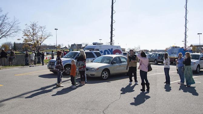 Spectators and media look toward the Azana Spa as police and swat team members respond to a call of a shooting at the Azana Spa in Brookfield, Wis. Sunday , Oct. 21, 2012.  Multiple people were wounded when someone opened fire at the spa near the Brookfield Square Mall. Deputies are still looking for the gunman. (AP Photo/Tom Lynn)