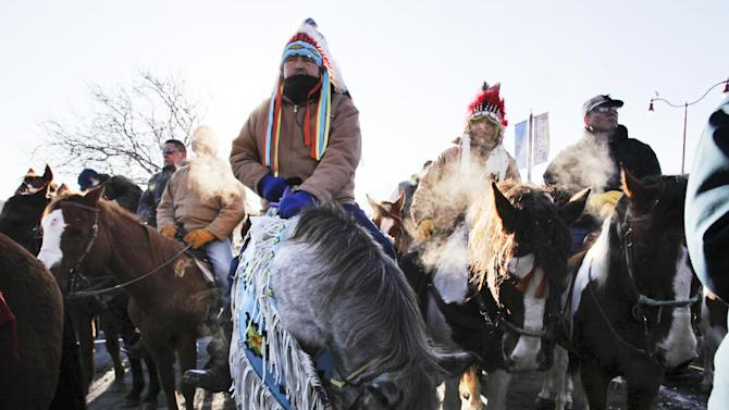 """Riders Gus High Eagle, center left, and Carl Mazawasicuna, center right, both of Canada, sat on their horses and listened in following The Dakota Wokiksuye Memorial Ride during a ceremony at Reconciliation Park, Wednesday, Dec. 26, 2012, in Mankato, Minn. The annual ride commemorates the 38 + 2 Dakota warriors hanged following the Dakota War of 1862. The """"Dakota 38"""" Memorial lists the names of all the Dakota warriors hanged in 1862. (AP Photo/The Star Tribune, David Joles)"""