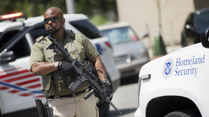 A US Marshal takes his position outside the federal court in Washington before the vehicles reportedly transporting the Libyan militant Ahmed Abu Khattala leave following Khattala's detention hearing, Wednesday, July 2, 2014. (AP Photo/Pablo Martinez Monsivais)