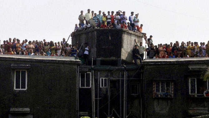 People crowd the roof top of a building to watch the funeral procession of Hindu hardline Shiv Sena party leader Bal Thackeray in Mumbai, India, Sunday, Nov. 18, 2012. Thackeray, the extremist leader linked to waves of mob violence against Muslims and migrant workers in India, died Saturday after an illness of several weeks. He was 86. (AP Photo) INDIA OUT