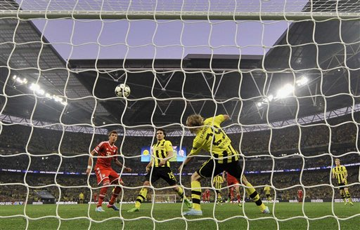 Bayern's Mario Mandzukic of Croatia, left, scores during the Champions League Final soccer match between  Borussia Dortmund and Bayern Munich at Wembley Stadium in London, Saturday May 25, 2013